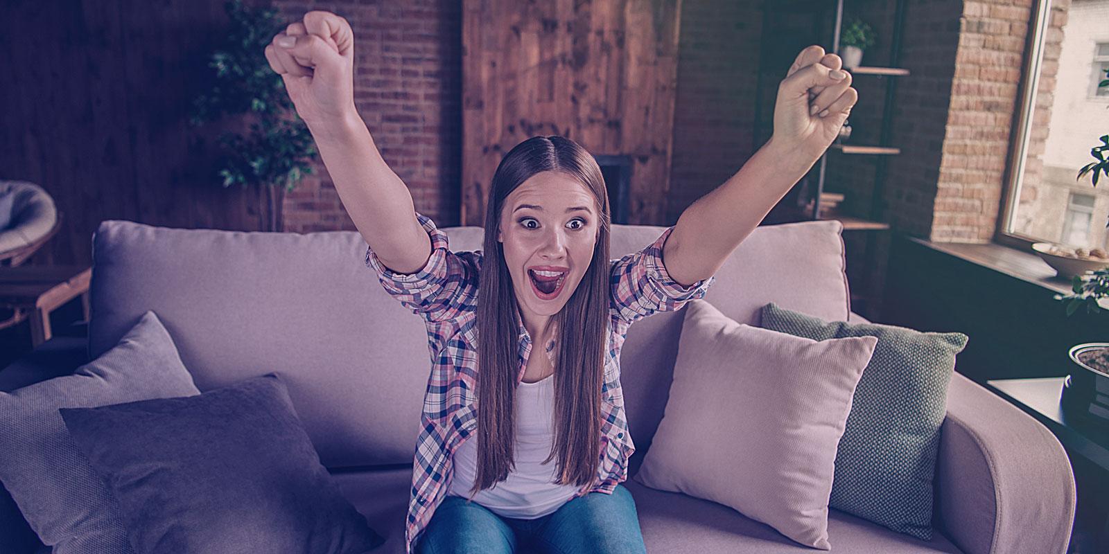 Begeisterte Frau auf einer Wohnzimmer Couch