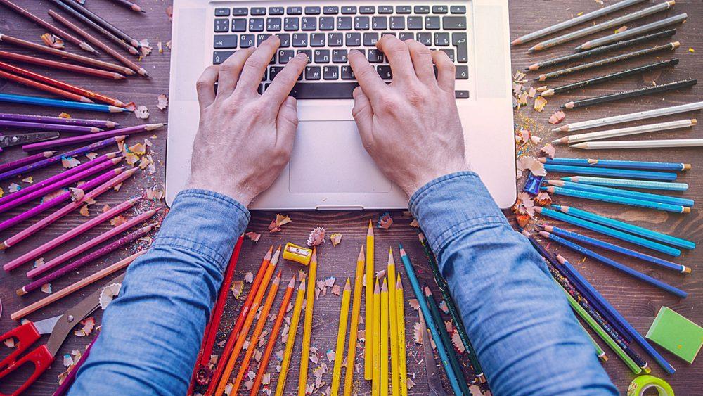 Hände liegen auf einem Laptop, um den Laptop liegen farbige Stifte