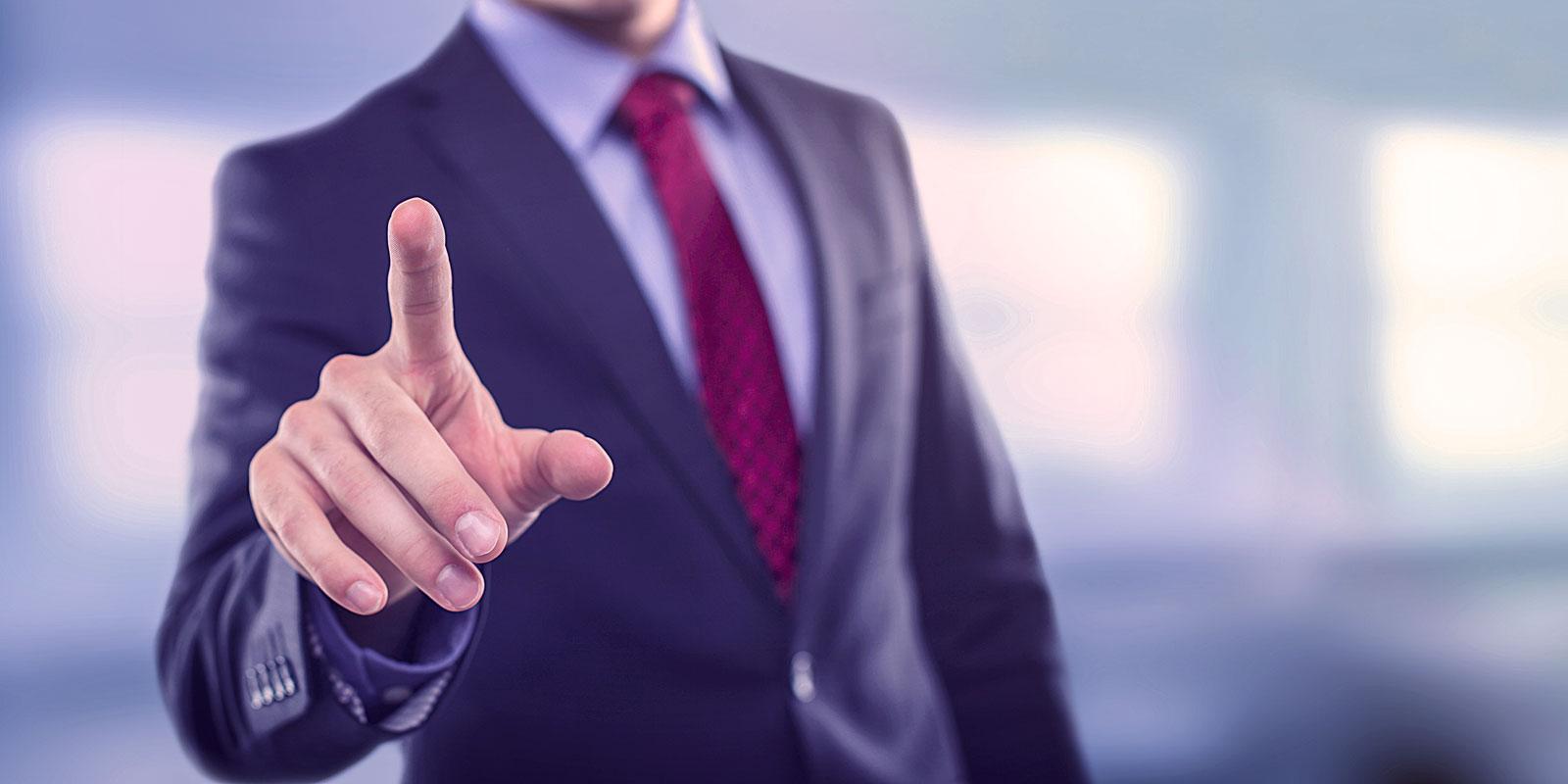 Businessmann mit Anzug und Krawatte zeigt mit den Zeigefinger in die Kamera