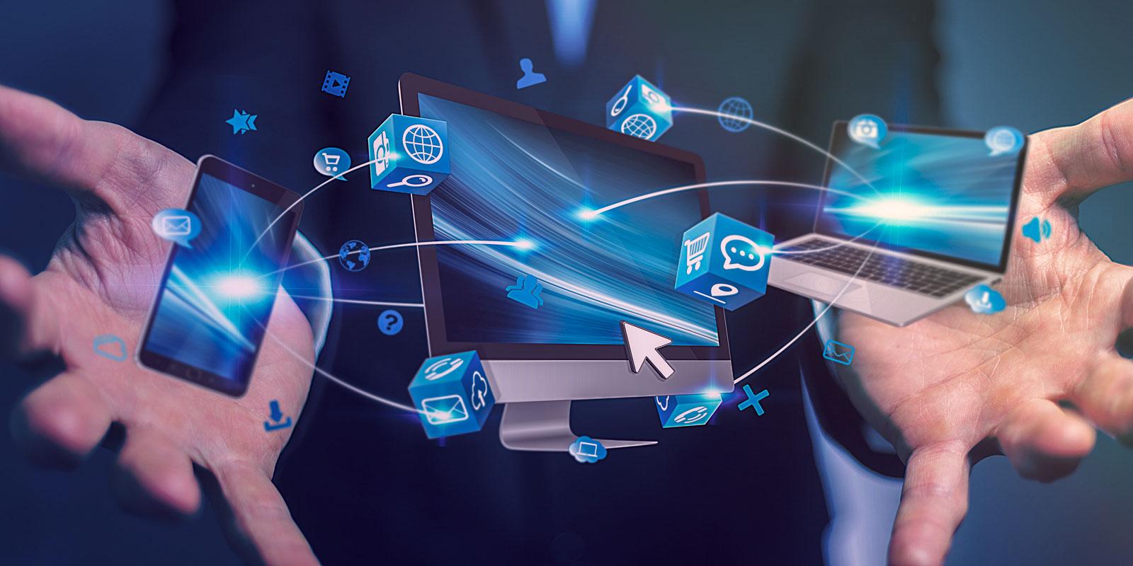 Verschiedene Eingabegeräte, Smartphones und Bildschirme schweben zwischen zwei Händen