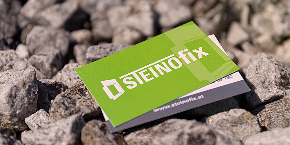 Steinofix Visitenkarten liegen auf Steinen